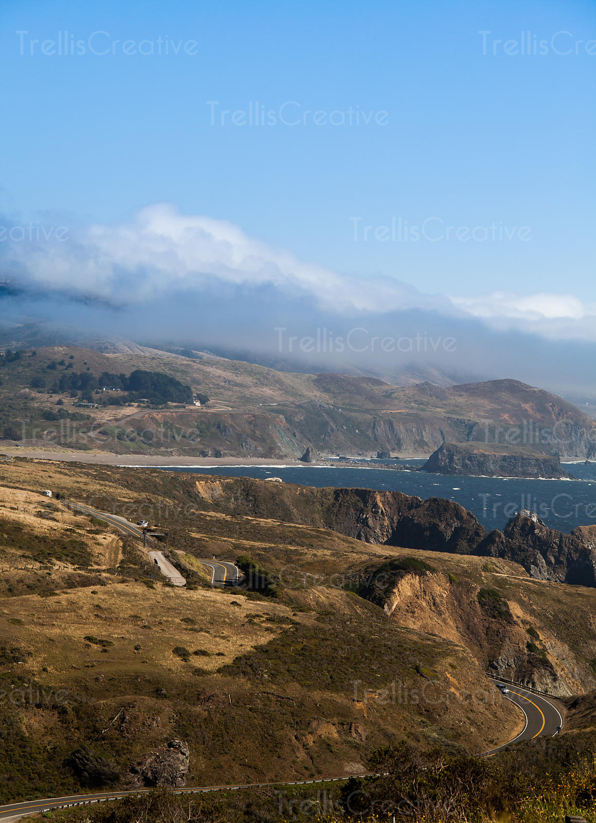 Fog lifts over the hills of the Great Highway along California's coastline.