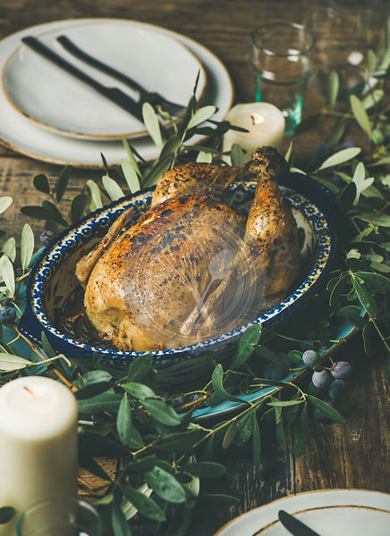 Whole roasted chicken in tray for Christmas eve celebration decorated with olive tree branch, plates, glasses and candles