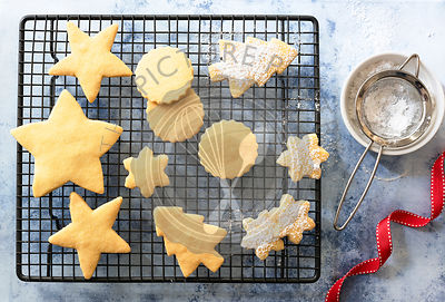 Different shaped Christmas Shortbread biscuits partially covered with icing sugar.