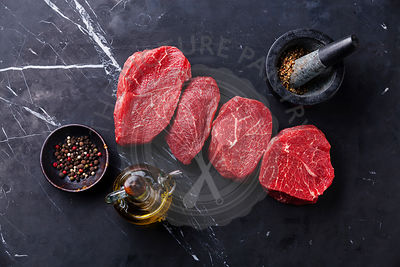 Raw fresh marbled meat Steak and seasonings on dark marble background