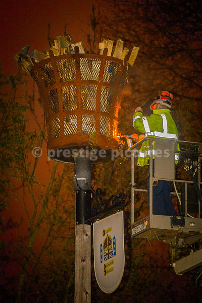 Workman in yellow hi-ves vest on high access platform lighting the VE Day Beacon n Banbury, Oxfordshire