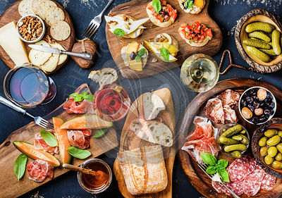 Italian antipasti wine snacks set over black grunge background, top view