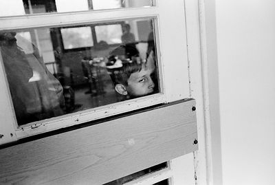 A boy peers from hos classroom at the Blind School