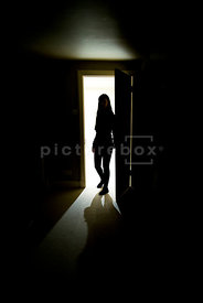 An atmospheric image of the silhouette of a girl standing in the doorway into a dark room.