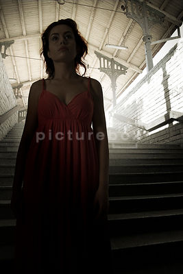 An atmospheric image of a mystery woman, in a red dress, standing on some steps in an old train station.