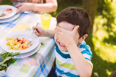 Boy covering his eyes on a garden party