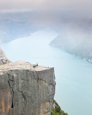 Person stretching after waking up on the Pulpit Rock, 604 meters above the Lysefjorden, Rogaland, Norway, Scandinavia, Model ...