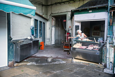 A butcher feeds scraps to the market cats at the Mercado do Bolhão, Porto, Portugal.