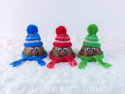Beautifully decorated Christmas puddings on snow