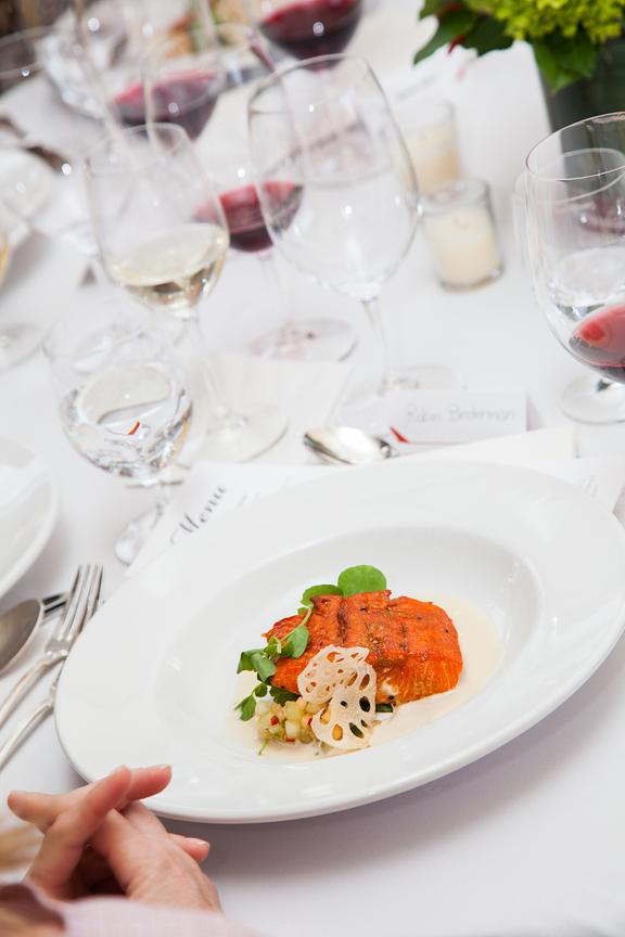 Colorful salmon dinner on a crisp white plate and tablecloth.