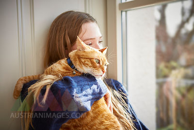 Female teenager with cat looking through window