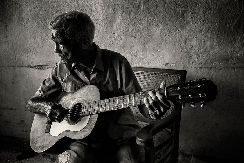 Eusebio Playing Guitar in his Home