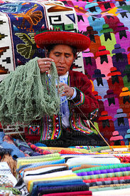 Quechua women wearing traditional dress sorting wool while selling handicrafts, Chinchero market, Sacred Valley, Cusco Region...
