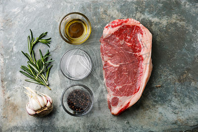 Raw fresh meat steak Striploin with rosemary, cooking oil, salt and pepper on stone slate background