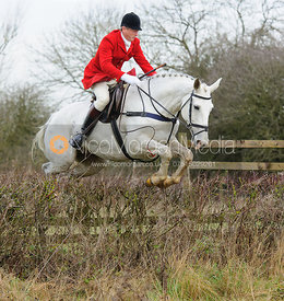 Nicholas Leeming jumping a hedge near Mrs Wilson's covert