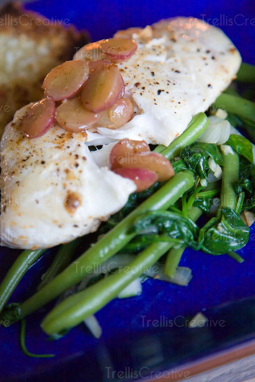 Pan seared halibut with warm grapes over steamed broccoli