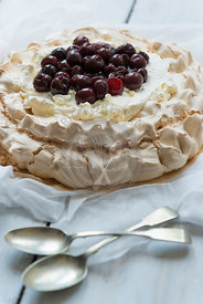 Baked pavlova with dark cherries.