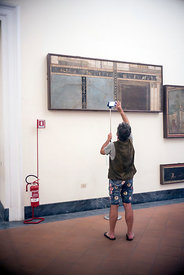 A tourist uses a 'selfie-stick' to photograph a frieze in the National Archaeological Museum in Naples