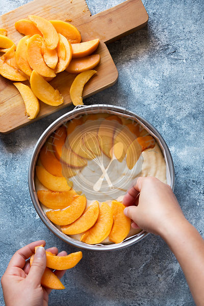 Female hands placing fresh sliced peaches over the batter in the pan.Top view