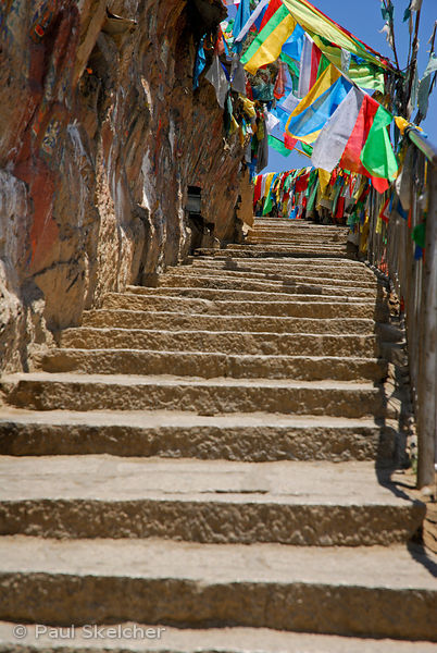 Path lined with prayer-flags and painted rock carvings is part of the sacred Lingkhor pilgrim circuit, encircling the old cit...