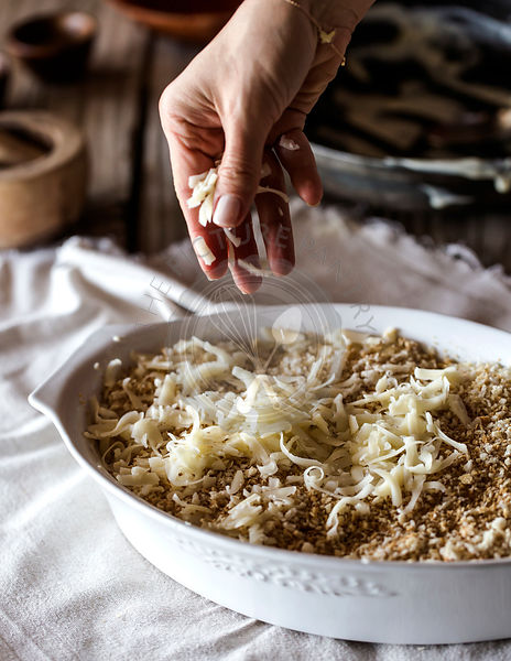 A woman is sprinkling cheese on a Spicy Cauliflower Gratin dish