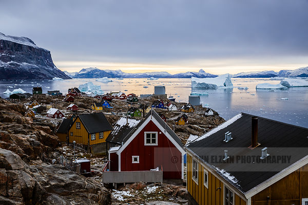 View on the town of Uummannaq with its colourful houses and icebergs floating in the fjord