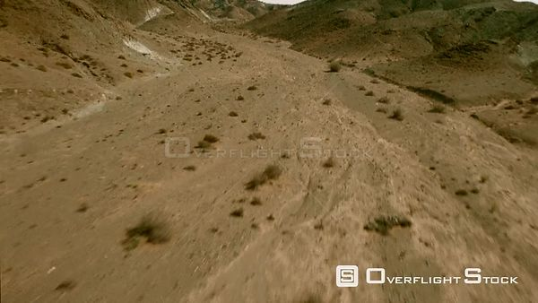 Aerial wide angle shot flying along a dry riverbed with sparse vegetation and mountains on each side, up side of mountain and...