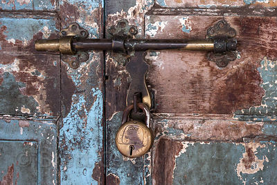 A weathered blue door and brass lock in Lalbaug, Mumbai, India.