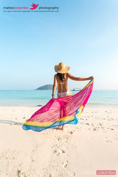 Woman in bikini with sarong walking on beach