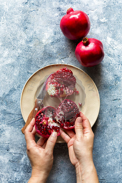 Female hands holding pomegranate slices.Top view