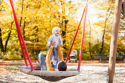 Happy baby girl relaxing with her mother on a swing in autumn
