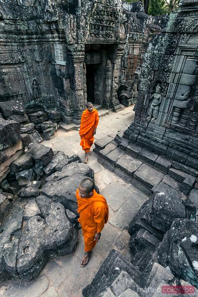Cambodia, Angkor Wat . Monks walking inside  temple