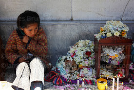 Girl sitting next to skulls in cemetery, Ñatitas festival, La Paz, Bolivia