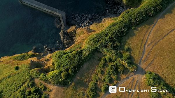 Camera looks down as drone descends towards cliff and harbor wall of Port Isaac in Cornwall with beautiful morning light