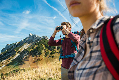 Austria, Tyrol, Tannheimer Tal, young man on hiking trip looking through binocular