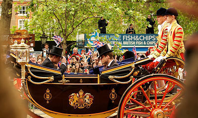 Prince William and Prince Harry in and open Carriage tipping their top hats to each other while two footmen look on