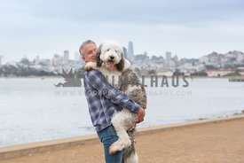 dog dad holding huge sheepadoodle puppy in front of San Francisco skyline