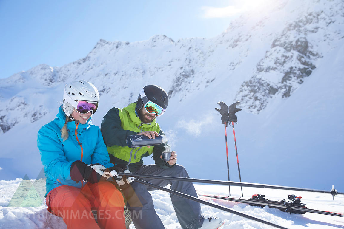 Austria, Tyrol, Kuehtai, two skiers in winter landscape having a break
