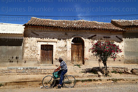 Local man cycling past old colonial house, Tarata, Cochabamba Department, Bolivia