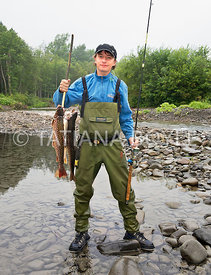 Sport fisherman with his catch; Central Sakhalin, Russia