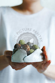 A woman holding a bowl of mixed matcha and chocolate homemade sweets