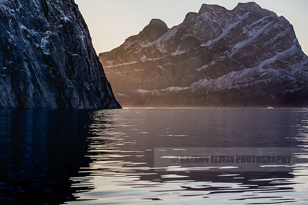 A fishing boat comes at full speed between two vertical cliffs in the Uummannaq fjord in Greenland
