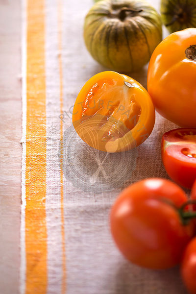 Variety of tomatoes whole and cut on rustic linen. Light, summery feel.