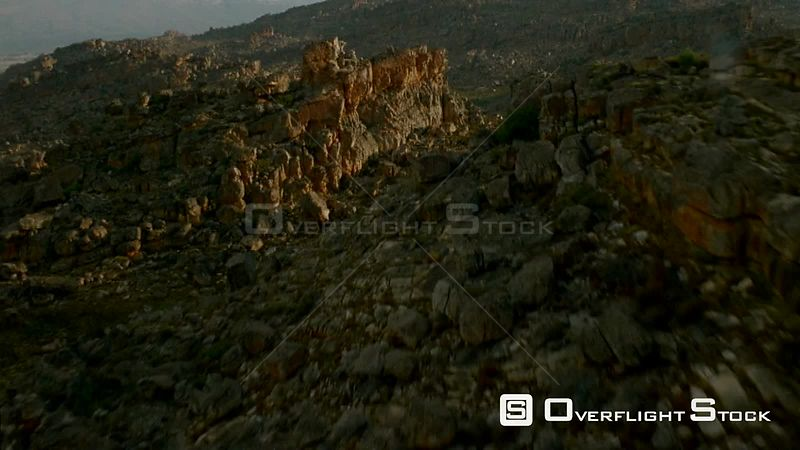 Aerial wide angle shot rocky terraced mountain terrain with grassed plains between outcrops Botswana