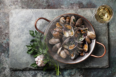 Shells vongole venus clams with parsley in copper cooking dish on stone slate background
