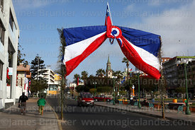 Banner in colours of Chilean flag over street for 18th September Independence Day celebrations, Plaza Colon, Arica, Region XV...