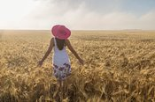 Woman with pink hat in wheat field in a misty morning