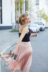 Portrait of laughing woman with high heels and clutch bag in her hand walking on the street