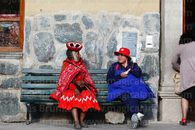 Two women in contrasting clothing sitting on a bench in Ollantaytambo, Sacred Valley, Peru