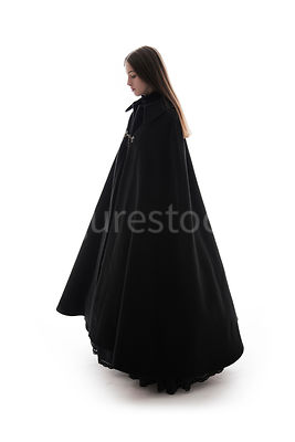 A woman in a big cloak standing and looking down – shot from eye level.
